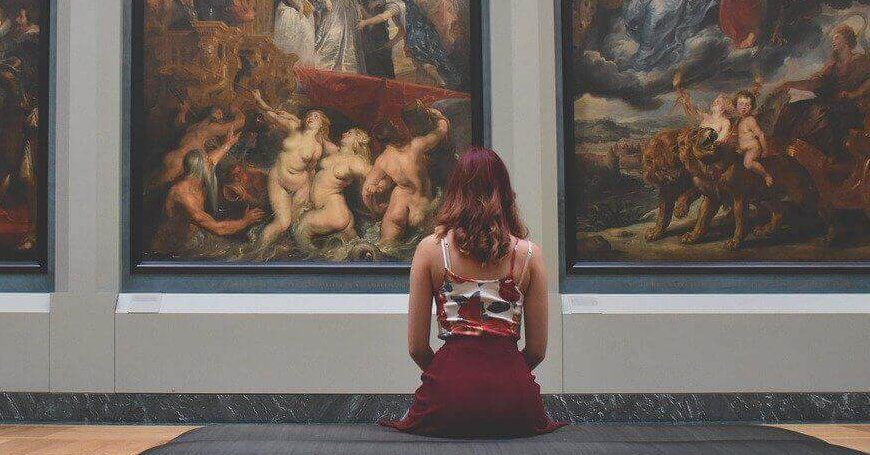 Devojka sedi na klupi ispred slike u galeriji