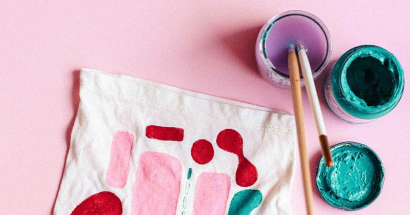 Četkice, boje i tekstil na roze pozadini