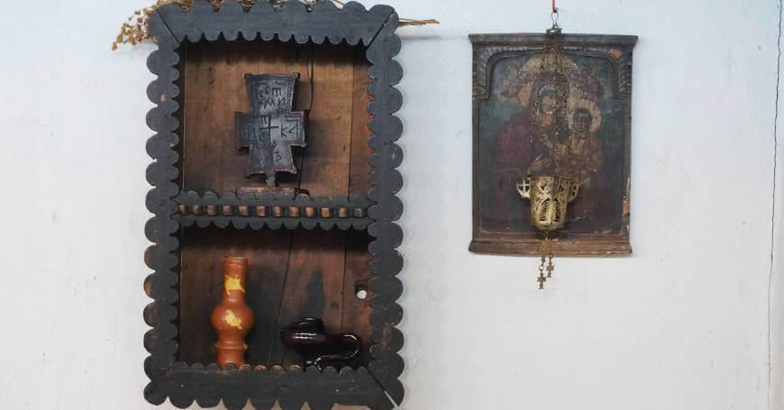 Ikona bogorodice i okačene police na zidu sa kandilom i krstom