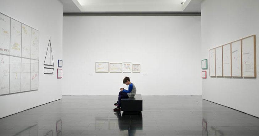 Dečak u muzeju sam sedi i gleda izložbu